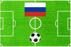 Drapeau russe sur le fond d'un terrain de football Photos stock