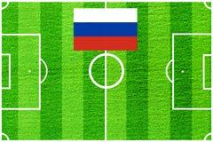 Drapeau russe sur le fond d'un terrain de football Photographie stock