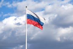 Drapeau russe sur le mât de drapeau ondulant sur le ciel nuageux Photo libre de droits