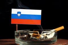 Drapeau slovène avec la cigarette brûlante dans le cendrier sur le noir Photographie stock