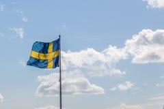 Drapeau suédois ondulant devant le ciel nuageux Photos stock