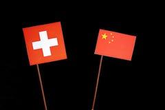 Drapeau suisse avec le drapeau chinois sur le noir Photo stock