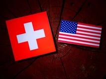 Drapeau suisse avec le drapeau des Etats-Unis sur un tronçon d'arbre Photographie stock