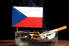 Drapeau tchèque avec la cigarette brûlante dans le cendrier d'isolement sur le noir Image stock