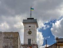Drapeau ukrainien en haut de la tour d'horloge d'hôtel de ville de Lviv, Ukraine, avec un fond nuageux Images stock