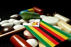 Drapeau zimbabwéen avec le sort de pilules médicales d'isolement sur le noir Photo libre de droits