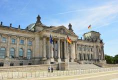 Drapeaux allemands ondulant dans le vent au bâtiment de Reichstag, siège du Parlement allemand Deutscher Bundestag, un jour ensol Photo stock