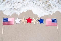 Drapeaux américains avec des étoiles de mer sur la plage sablonneuse Image stock