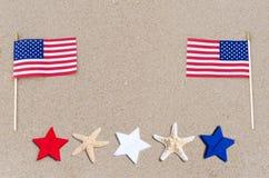 Drapeaux américains avec des étoiles de mer sur la plage sablonneuse Images libres de droits