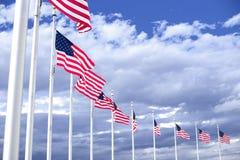 Drapeaux américains s'enroulant sur le ciel bleu Photographie stock libre de droits
