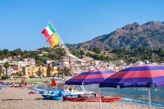 Drapeaux au-dessus des bateaux et des personnes sur la plage Image libre de droits