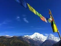 Drapeaux bouddhistes de prière en montagnes de l'Himalaya, ciel bleu d'espace libre et montagnes blanches Photos stock