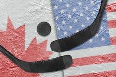 Drapeaux canadiens et américains, et hockey de deux bâtons de hockey Photo libre de droits