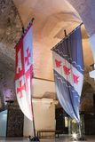 Drapeaux chevaleresques avec des manteaux d'ensemble de bras dans les halls dans les ruines de la forteresse dans la vieille vill Image stock