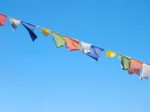 Drapeaux colorés de prière au-dessus d'un ciel bleu clair dans l'Inde Photo stock