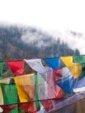 Drapeaux colorés de prière au-dessus de l'Himalaya brumeux au Bhutan Photos stock