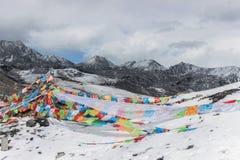 Drapeaux colorés de prière sur la montagne de neige photos stock