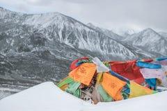 Drapeaux colorés de prière sur la montagne de neige Image libre de droits
