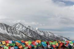Drapeaux colorés de prière sur la montagne de neige Photographie stock