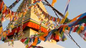 Drapeaux colorés de prière volant dans le vent chez Boudhanath Stupa, pagoda sainte, symbole du Népal et Katmandou avec le golgen banque de vidéos