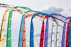 Drapeaux colorés ondulant dans le vent Fond de ciel nuageux Images stock