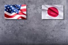 Drapeaux d'Américain et du Japon Drapeau des Etats-Unis et du Japon sur le backgro concret Images stock