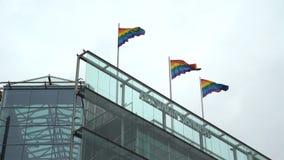 Drapeaux d'arc-en-ciel à l'appui d'égalité sur le toit d'un gratte-ciel au centre de la ville clips vidéos