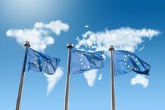 Drapeaux d'UE contre la carte du monde faite de nuages Images stock