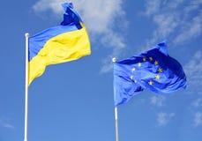 Drapeaux d'UE de l'Ukraine et de l'Union européenne contre le ciel bleu photos stock