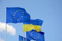 Drapeaux d'UE de l'Ukraine et de l'Union européenne contre le ciel bleu photos libres de droits