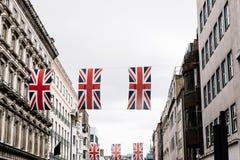 Drapeaux d'Union Jack accrochant dans la ville de Londres images libres de droits