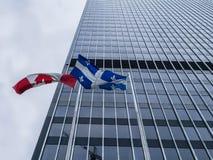 Drapeaux de Canadien et du Québec devant un gratte-ciel Images stock