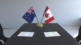 Drapeaux de l'Australie et du Canada et papiers sur la table Négociations et signature d'un accord international Conceptuel illustration stock