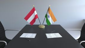 Drapeaux de l'Autriche et de l'Inde et papiers sur la table Négociations et signature d'un accord international 3D conceptuel illustration libre de droits