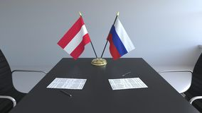 Drapeaux de l'Autriche et de la Russie et papiers sur la table Négociations et signature d'un accord international 3D conceptuel illustration libre de droits