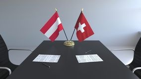Drapeaux de l'Autriche et de la Suisse et papiers sur la table Négociations et signature d'un accord international illustration libre de droits
