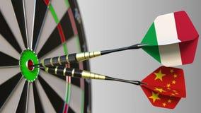 Drapeaux de l'Italie et de la Chine sur des dards frappant la boudine de la cible Coopération internationale ou concurrence 3D co Photographie stock