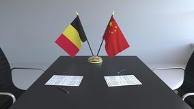 Drapeaux de la Belgique et de la Chine et papiers sur la table Négociations et signature d'un accord international 3D conceptuel illustration de vecteur