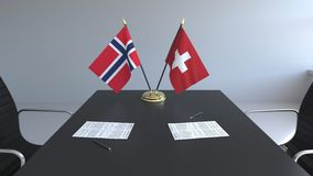 Drapeaux de la Norvège et de la Suisse et papiers sur la table Négociations et signature d'un accord international Conceptuel illustration stock