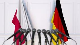 Drapeaux de la Pologne et de l'Allemagne à la réunion ou à la conférence internationale rendu 3d Photographie stock libre de droits