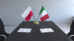 Drapeaux de la Pologne et de l'Italie et papiers sur la table Négociations et signature d'un accord international 3D conceptuel illustration libre de droits