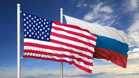 Drapeaux de ondulation des Etats-Unis et de la Russie sur le mât de drapeau Photo stock