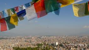 Drapeaux de ondulation de prière contre le paysage urbain Vue d'onduler les drapeaux multicolores de prière sur des ficelles au-d banque de vidéos