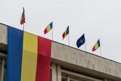 Drapeaux de Roumain et d'OTAN dans le vent Photographie stock