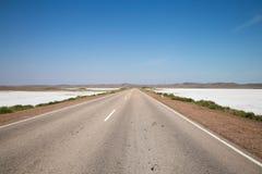 Drapeaux de sel d'assèche sur la route d'été avec la ruelle blanche sous le ciel nuageux Images stock