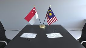 Drapeaux de Singapour et de la Malaisie et papiers sur la table Négociations et signature d'un accord international Conceptuel illustration stock