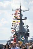 Drapeaux de vacances sur le navire de guerre russe et les personnes en vacances Photo stock