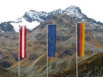Drapeaux de zone frontalière dans le paysage alpin Photographie stock libre de droits