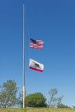 Drapeaux des USA et de la Californie au demi mât Photos stock