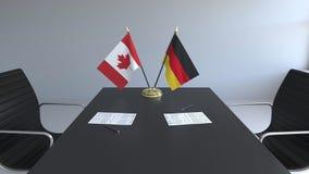 Drapeaux du Canada et de l'Allemagne et papiers sur la table Négociations et signature d'un accord international 3D conceptuel illustration stock